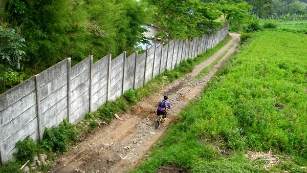 Ada yang menuruni jalan dengan menaiki sepedanya.