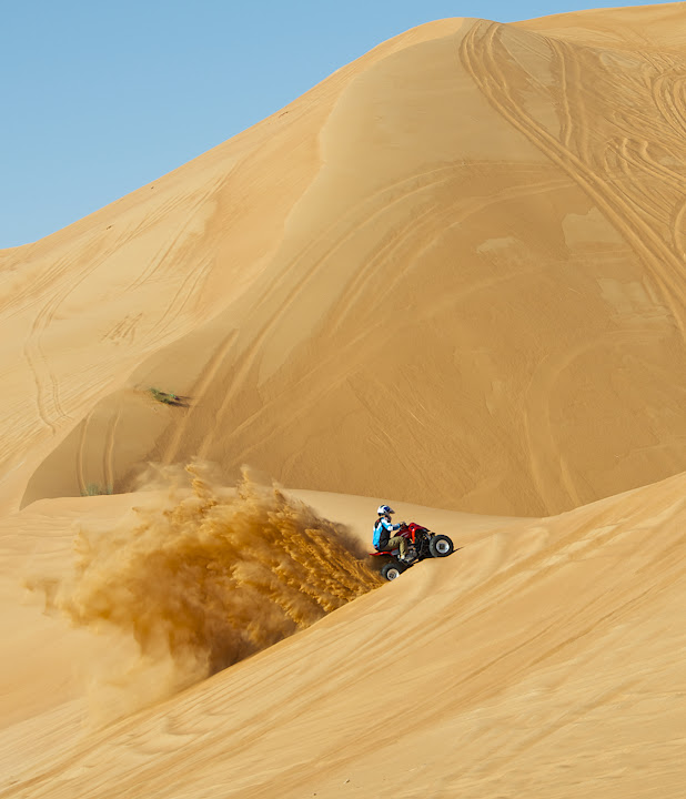 Quad climbing sharp dune