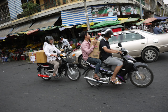 people carrying boxes while riding motorbikes in Phnom Penh