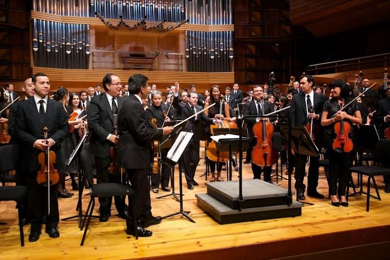 Al final de la presentación, la orquesta venezolana y el director Joshua Dos Santos sonríen de pie al recibir los aplausos del público
