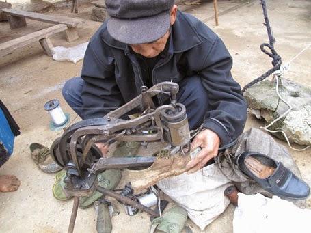 Sửa chữa tại chỗ những đôi giày vượt núi còn vương bùn của người đi chợ sớm.