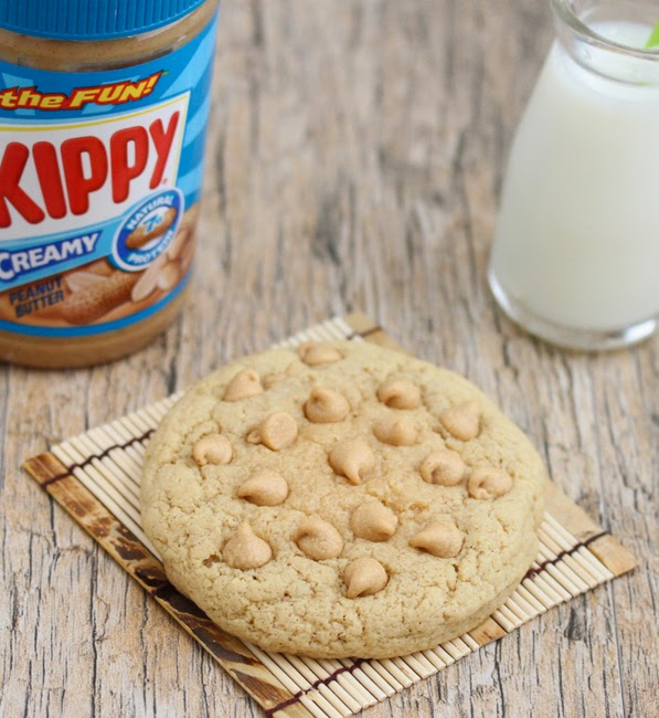 photo of a cookie with a jar of peanut butter and a glass of milk in the background