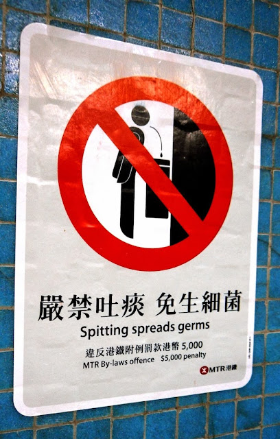 """No spitting"" sign in Hong Kong with text ""Spitting spreads germs"""