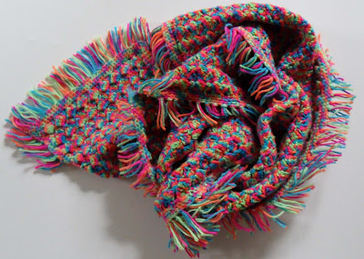 Multicoloured crochet scarf with fringe edge all the way around. Colours are blue, turquoise, vivid green, orange, red, purple, pink. Should only be worn by someone very brave.