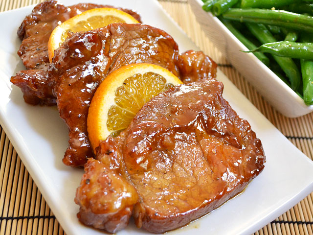 orange molasses chops plated on plate with orange slices