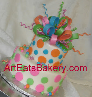 two tier pink, blue, green and orange polka dot engagment party cake with sugar bow topper