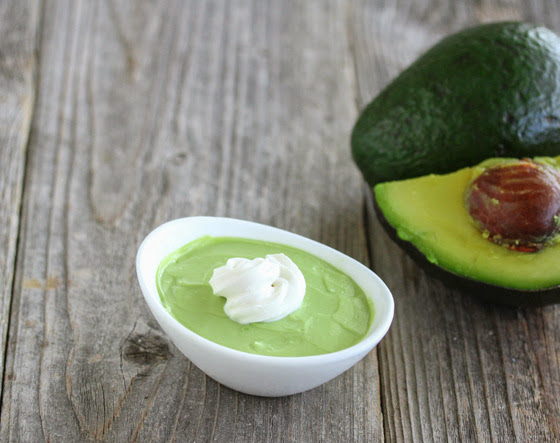 photo of a bowl of Avocado Coconut Mousse with avocados in the background