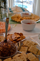 The appetizer table looks delicious with crackers and dip and shrimp.