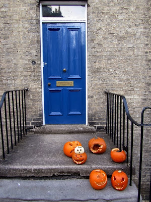 Carved pumpkins by a doorway