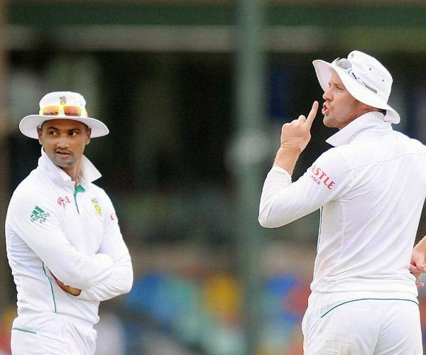 South African cricketer AB de Villiers (R) gestures in reaction to spectators as teammate Alviro Petersen (L) looks on during the opening day of the second Test match between Sri Lanka and South Africa at the Sinhalese Sports Club (SSC) Ground in Colombo on July 24, 2014.