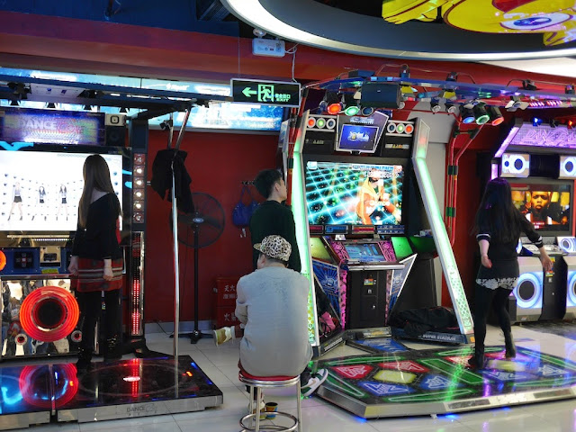 people playing dance video games in D-Mall in Shanghai