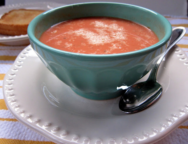 Creamy Tomato Soup recipe - delicious homemade tomato soup that is ready in under 20 minutes! Chicken broth, tomato puree, onion, garlic, red pepper flakes, oregano, basil, cream cheese and milk. I use low fat cheese and milk and it tastes great!! Serve with a grilled cheese sandwich for a quick weeknight meal.