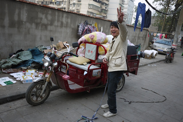 man in front of his motor tricycle cart in Changsha, China