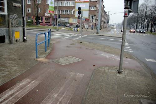 Skrzyżowanie dróg dla rowerów (z czerwonego asfaltu) oddzielone barierkami od chodnika