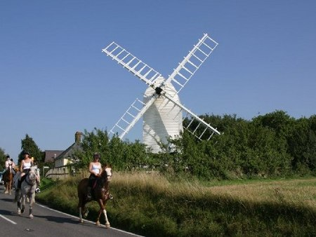 Horse riders passing windmill