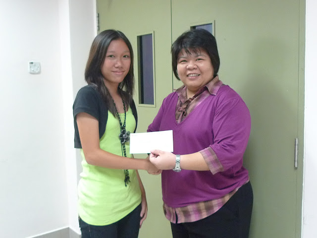 Song Cai Feng (left) receiving the Bursary Award from Ms Siau, EXCO member of AJCAA and VP of AJC.
