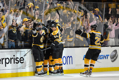 Bruins players celebrate Brad Marchand's overtime winning goal
