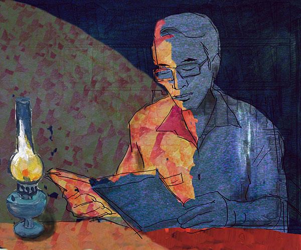 Ảnh thầy giáo đang ngồi đọc sách dưới ngọn đèn dầu
