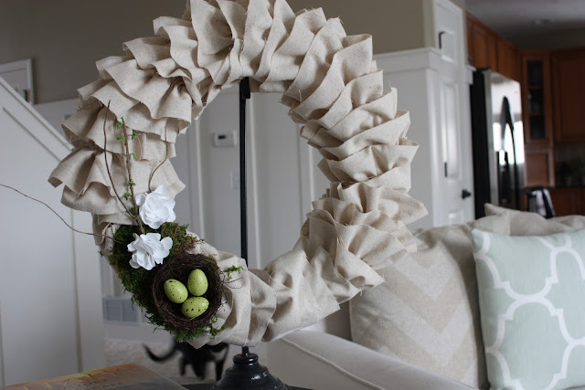 The wreath on a stand in the living room beside the couch.