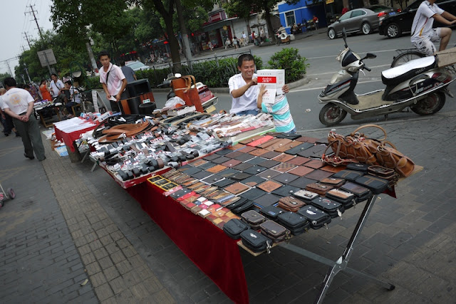 wallets and belts for sale on a sidewalk in Dachang Town, Shanghai