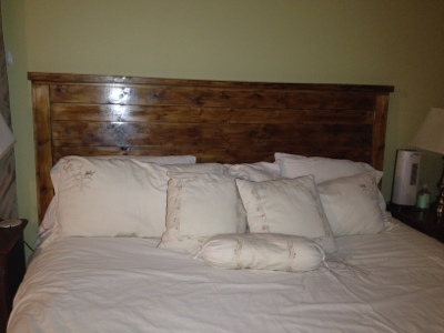 A finished picture of a wood headboard after staining a dark walnut color in a bedroom