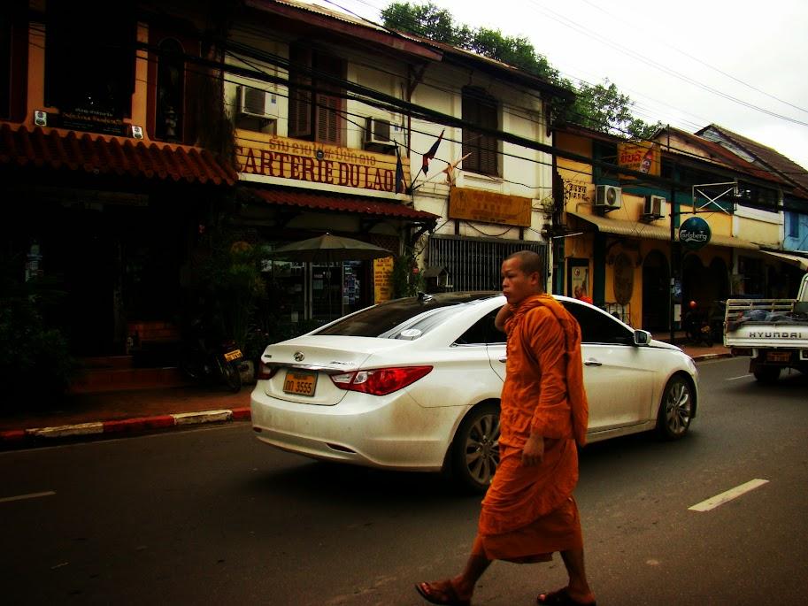 Monje budista cruzando como puede hacia cafetería con cartel en francés