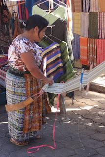 Des femmes tissent dans la rue des tissus locaux