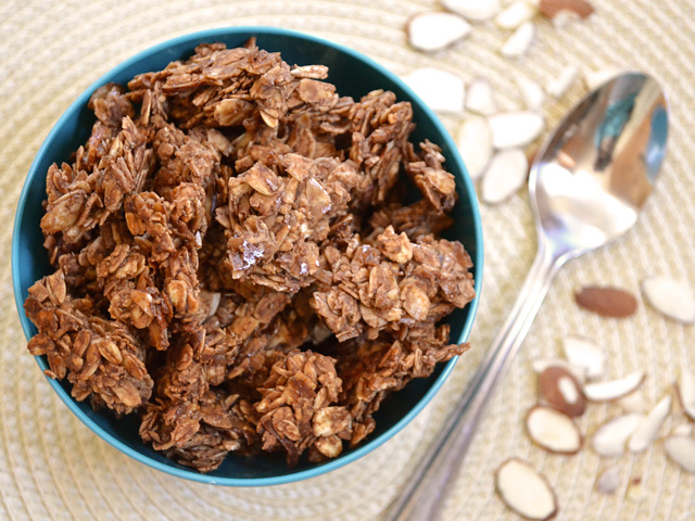 Top view of a bowl of Choco-Coconut Granola with spoon on the side