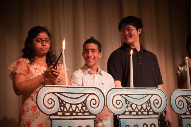 8th grade students lighting candles for each pillar of East-West during stepping up ceremony