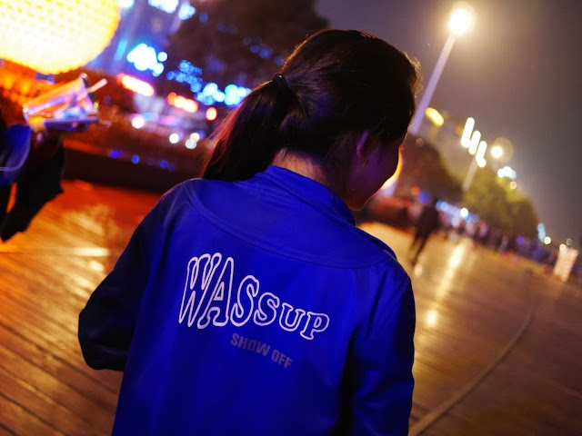 "girl wearing a light jacket with the words ""WASSUP SHOW OFF"" on the back"