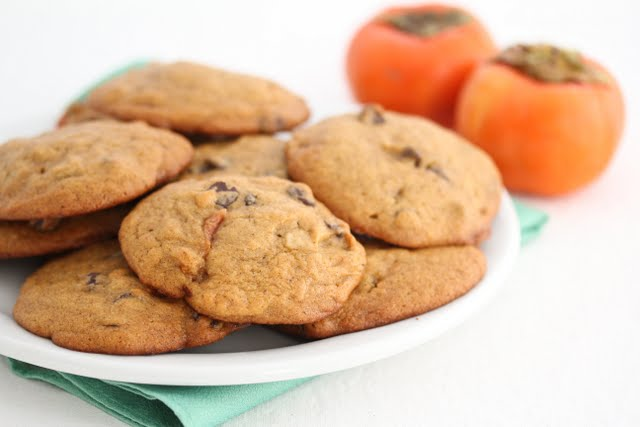 close-up photo of a plate of cookies with two fresh persimmons in the background