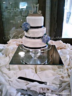 Three tier modern white wedding cake with navy blue ribbon and blue hydrangeas with wood carved monogram topper