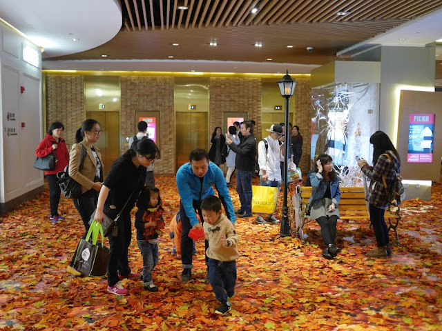 adults and children enjoying fake autumn leaves at a mall