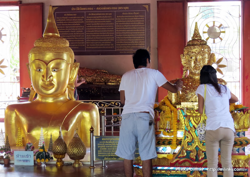Young couple adding gold to the Buddha image