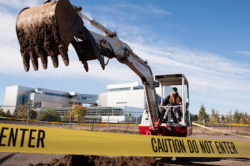 A student operates an excavator at Construction and Utilities Career Day.