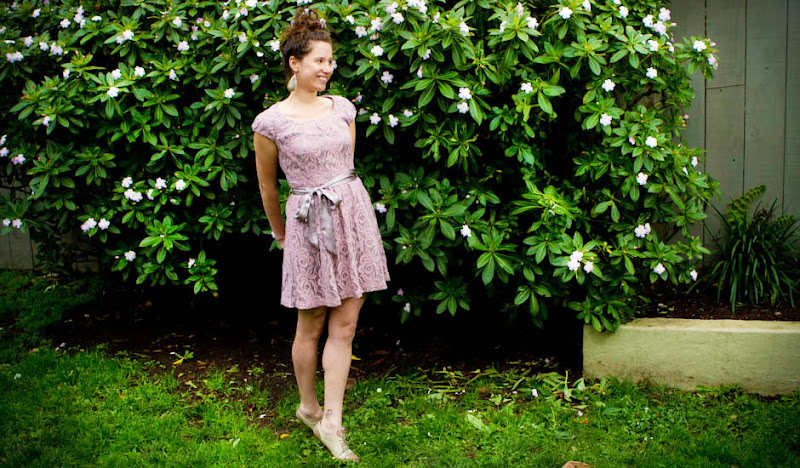 An Extremely Good Looking Woman in a Rose Dress in Front of a Bush