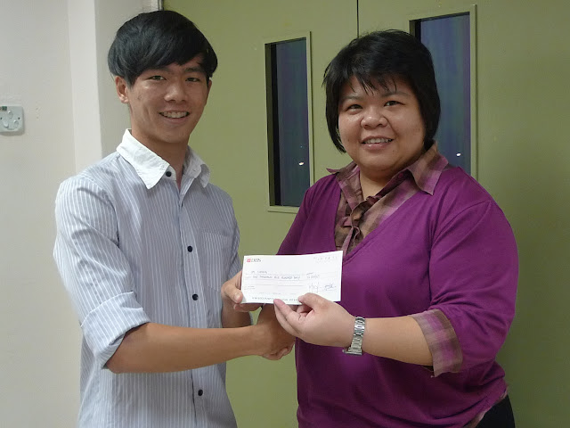 Cai Yiming (left) receiving the Bursary Award from Ms Siau, EXCO member of AJCAA and VP of AJC.