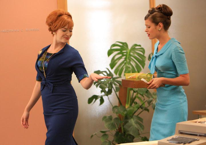 Joan Holloway luciendo un vestido azul muy ceñido (como de costumbre)