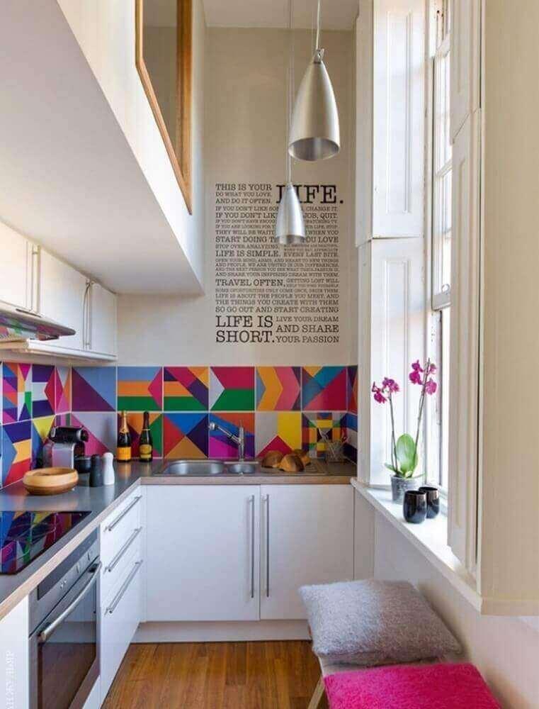Vista recortada do canto de uma cozinha. Podemos identificar um fogão, cafeteira, pia e armários. Imagem para ilustrar a reforma de casas.