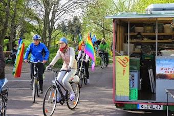 Radfahrerinnen und Radfahrer mit bunten Fahnen radeln am wartenden Friedensmobil vorüber.