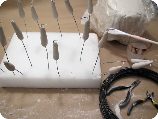 1. Start by preparing a bunch of 16 gauge hard wire stems about 7 inches long with one bend end. Roll clay in a quarter size ball and insert wire through the center.