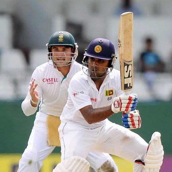 Sri Lankan batsman Mahela Jayawardene (R) plays a shot as South African cricketer Dean Elgar (L) looks on during the opening day of the second Test match between Sri Lanka and South Africa at the Sinhalese Sports Club (SSC) Ground in Colombo on July 24, 2014.