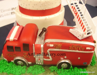 4 Tier white fondant wedding cake with silver pearls, red ribbons and 3D fire truck groom's cake with the ladder going up to the wedding cake close up