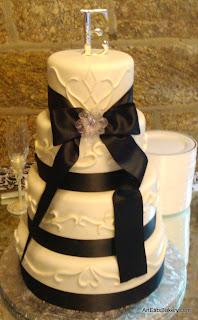 Four tier round fondant custom wedding cake with details from the brides dress, ribbone,, broach and mongram topper