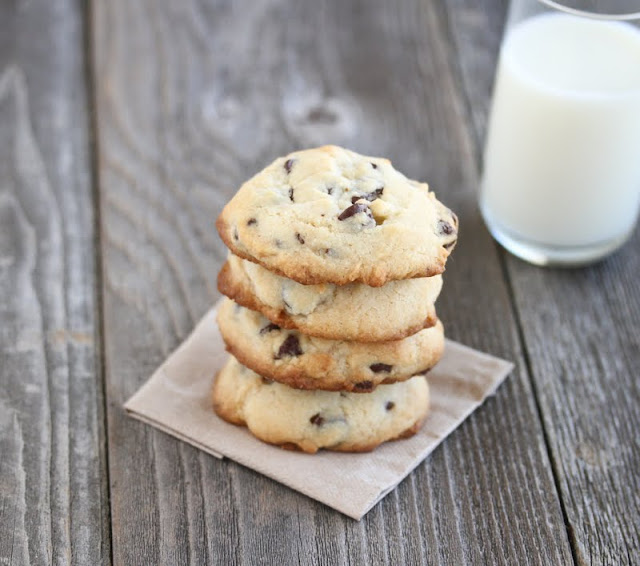 photo of a stack of chocolate chip cookies with a glass of milk