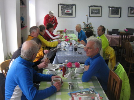 Cyclists at 4 tables in cafe