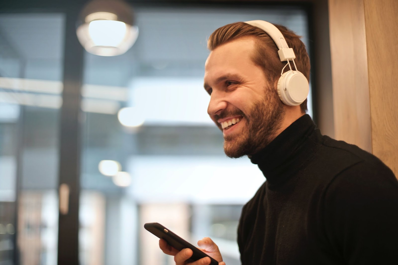 A picture of a man with headphones on, smiling and holding his phone in his hand: Getting your music on Spotify
