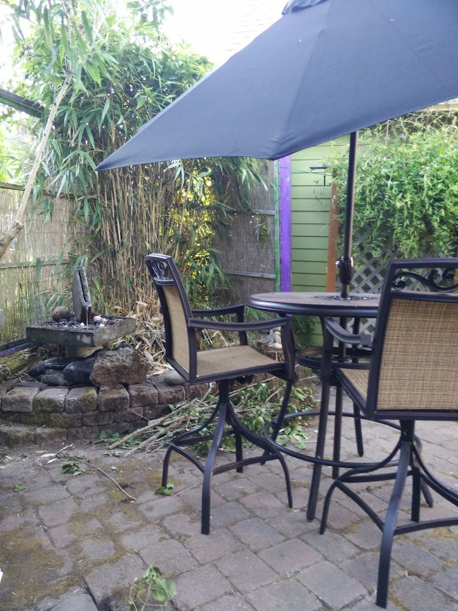 DarkEm's tiny hardscaped back yard with a table, a black umbrella, some chairs, and a fountain