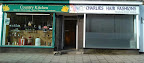 A pair of shopfronts, green healthfood & white hairdressers