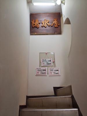 狭くて急な階段。途中には清水屋さんの看板とお得な本日のランチの案内がある